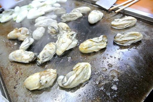 鉄板に投入される牡蠣